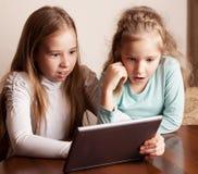 Niños que juegan en la tablilla Fotos de archivo