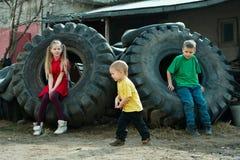 Niños que juegan en neumáticos del depósito de chatarra imagen de archivo libre de regalías
