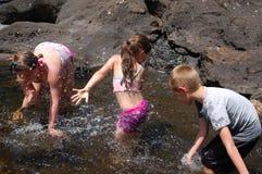 Niños que juegan en salpicar del arroyo Fotografía de archivo