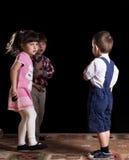 Niños que juegan en un fondo negro Imagen de archivo libre de regalías