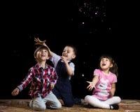 Niños que juegan en un fondo negro Imagenes de archivo