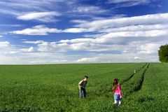 Niños que juegan en un prado.   Imagen de archivo libre de regalías