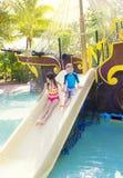 Niños que juegan en un tobogán acuático en un waterpark fotos de archivo