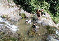 Niños que juegan en una cascada Imagenes de archivo