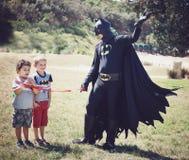 Niños que juegan en una fiesta de cumpleaños de los niños con el super héroe del hombre del palo Imagen de archivo libre de regalías