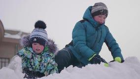 Niños que juegan en una montaña nevosa, una nieve que lanza y un smejutsja Día escarchado soleado Diversión y juegos en el aire f almacen de metraje de vídeo