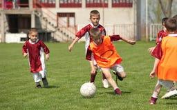 Niños que juegan a fútbol Fotografía de archivo libre de regalías