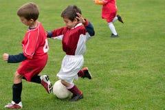 Niños que juegan a fútbol Fotos de archivo libres de regalías