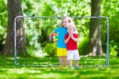 Niños que juegan a fútbol al aire libre Imagenes de archivo