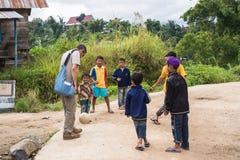 Niños que juegan a fútbol con el hombre adulto Foto de archivo libre de regalías