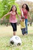 Niños que juegan a fútbol con su madre Fotografía de archivo
