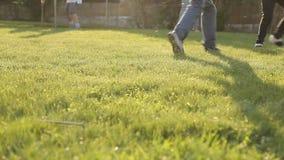 Niños que juegan a fútbol con una bola en la hierba almacen de metraje de vídeo