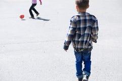 Niños que juegan a fútbol en el asfalto, jugador de equipo de fútbol, entrenando a forma de vida al aire libre, activa Imagen de archivo