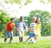 Niños que juegan a fútbol en el parque Fotos de archivo