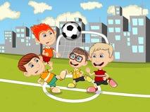 Niños que juegan a fútbol en la historieta del parque Imagenes de archivo