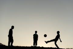 Niños que juegan a fútbol en la naturaleza Imagen de archivo