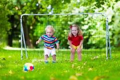 Niños que juegan a fútbol en patio de escuela Foto de archivo