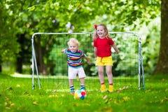 Niños que juegan a fútbol en patio de escuela Imágenes de archivo libres de regalías