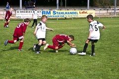 Niños que juegan a fútbol en una arena al aire libre de la hierba Foto de archivo libre de regalías
