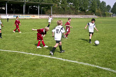 Niños que juegan a fútbol en verano Imagenes de archivo