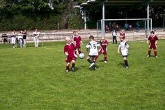 Niños que juegan a fútbol en verano Fotos de archivo libres de regalías