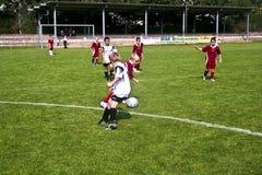 Niños que juegan a fútbol en verano en una arena al aire libre de la hierba Imagen de archivo libre de regalías