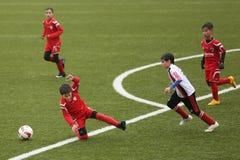Niños que juegan a fútbol o a fútbol Foto de archivo