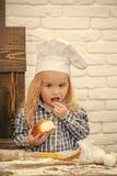 Niños que juegan - juego feliz Cocinero del muchacho en sombrero del cocinero en cocina Imagen de archivo libre de regalías