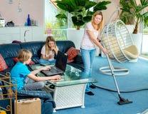 Niños que juegan a juegos electrónicos y madre que hace la preparación Fotos de archivo