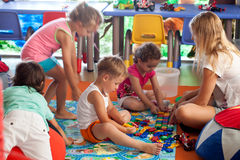 Niños que juegan a juegos en cuarto de niños Imagen de archivo