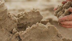 Niños que juegan la arena en la playa La niña construye el castillo de la arena solo en la playa metrajes