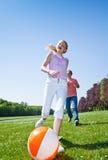 Niños que juegan la bola en un parque Fotografía de archivo libre de regalías