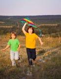 Niños que juegan la cometa en prado de la puesta del sol del verano Foto de archivo libre de regalías