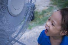 Niños que juegan la fan eléctrica y que gozan del aire fresco en la estación de verano foto de archivo libre de regalías