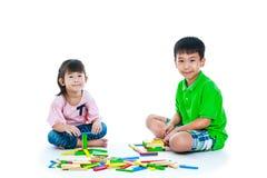 Niños que juegan los bloques de madera del juguete, aislados en el fondo blanco Foto de archivo