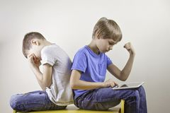 Niños que juegan a los juegos de ordenador con la tableta Un triunfo del muchacho el juego y la otra sentada cansó e infeliz desp Imágenes de archivo libres de regalías