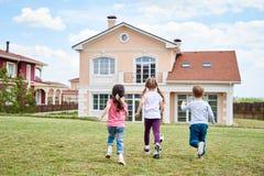 Niños que juegan por la casa hermosa Imagen de archivo