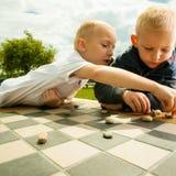 Niños que juegan a proyectos o al juego de mesa de los inspectores al aire libre Fotos de archivo libres de regalías