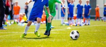 Niños que juegan a un juego de fútbol Fútbol de retroceso con el pie del fútbol de Young Boys Imagen de archivo