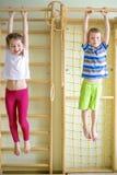 Niños que juegan y que cuelgan en barra horizontal fotografía de archivo