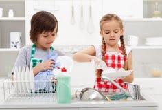 Niños que lavan los platos en la cocina Imagen de archivo
