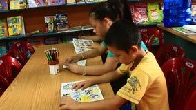 Niños que leen en biblioteca metrajes