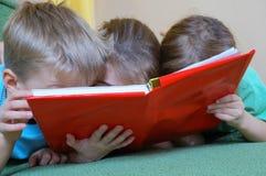 Niños que leen un libro Imagen de archivo libre de regalías