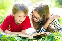 Niños que leen un libro Fotos de archivo libres de regalías