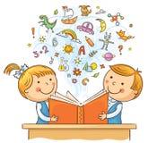 Niños que leen un libro junto Imágenes de archivo libres de regalías