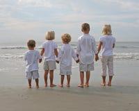 Niños que llevan a cabo las manos en la playa Fotografía de archivo libre de regalías