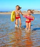 Niños que llevan a cabo las manos que corren en la playa. Fotografía de archivo