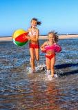 Niños que llevan a cabo las manos que corren en la playa Fotos de archivo