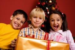 Niños que llevan el regalo de la Navidad Foto de archivo