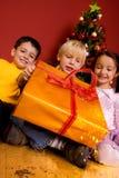 Niños que llevan el regalo de la Navidad Fotografía de archivo libre de regalías